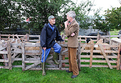 © Licensed to London News Pictures.26/08/15<br /> Egton, UK. <br /> <br /> Two men chat amongst the sheep pens at the 126th Egton Show in North Yorkshire. <br /> <br /> Egton is one of the largest village shows in the country and is run by a band of voluntary helpers. <br /> <br /> This year the event featured wrought iron and farrier displays, a farmers market, plus horse, cattle, sheep, goat, ferret, fur and feather classes. There was also bee keeping, produce and handicrafts on display.<br /> <br /> Photo credit : Ian Forsyth/LNP