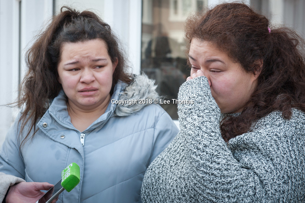 Longfellow Road, Stoke, Coventry, UK. 23rd February 2018. Floral tributes and messages of condolence are placed near the spot where two boys were killed by car in Coventry yesterday. The two brothers aged six and two died after a hit-and-run crash in the Stoke area of Coventry. /  Pictured: Paternal auties of the boys killed give an interview to the media outside their house opposite to the scene of the tradegy. Left: Tia Fletcher; Right: Chelsea Platt-May. // Lee Thomas, Tel. 07784142973. Email: leepthomas@gmail.com  www.leept.co.uk (0000635435)