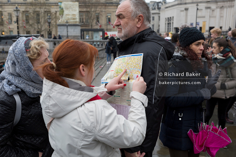 Tourists consult a map of London in Trafalgar Square, Westminster, on 9th April 2019, in London, England.