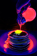 A dispenser pours glowing syrup on a stack of pancakes.Black light