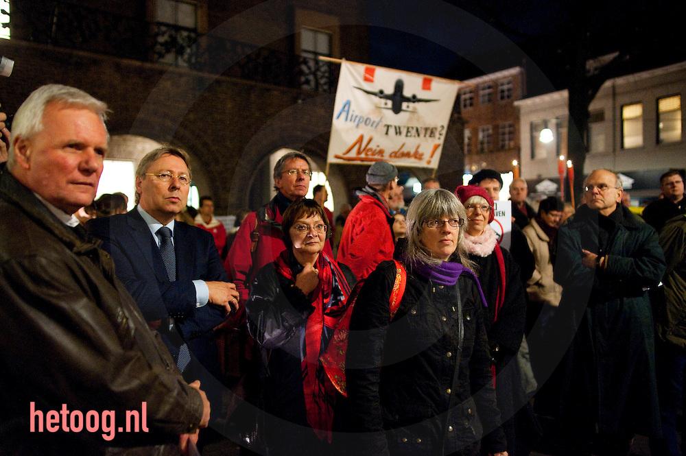 Burgemeester Den Oudsten (tweede van links) kijkt toe bij protest van twentenaren en duitsers tegen de doorstart van vliegveld twente als burgerluchthaven voorafgaand aan de commissie vergadering waarin de doorstart wordt besproken. Enschede stadhuisplein 30 nov 2009