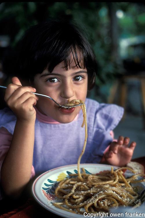 girl eating Bucatni with rabbit, in Ischia, near Naples - Photograph by Owen Franken
