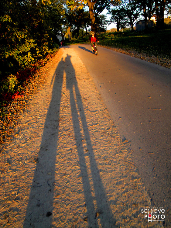 The shadows of two walkers on a University of Wisconsin-Madison path.