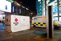 """© Licensed to London News Pictures . 16/12/2017. Manchester, UK. A mobile """" welfare unit """", offering people tea, coffee and medical support, is placed alongside an ambulance , on the pavement opposite the Printworks nightclub venue . Revellers out in Manchester City Centre overnight during """" Mad Friday """" , named for historically being one of the busiest nights of the year for the emergency services in the UK . Photo credit: Joel Goodman/LNP"""