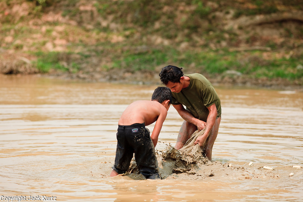 Mar. 12, 2009 -- VIENTIANE, LAOS: A father and son harvest fish from a freshwater fish pond in Vientiane, Laos. PHOTO BY JACK KURTZ