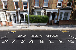 "© Licensed to London News Pictures. 09/07/2015. London, UK. Freshly painted minature double yellow lines in Mossbury Road, Clapham Junction. The tiny double yellow lines, measure approximately one foot in length and were repainted after Wandsworth Council resurfaced the road. There are two identical sets either side of a disabled parking bay. Owner of one of the properties behind the new road markings, Steven Taylor (not pictured) says ""They're so funny, what on earth could you park in there? They're not even big enough for a bike."" Photo credit : Vickie Flores/LNP"