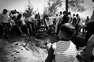 A young Syrian boy watches the burial of an FSA soldier who was shot close to Latakia. He later died in after crossing into Turkey on 7th of June. Yayaladagi, southern Turkey. 08/06/2012
