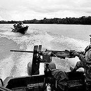 Naval gunboats patrol along the Rio Atrato in an attempt to disrupt the movement of the left and rightwing militia groups fighting in the area. Both groups use the river to move troops, weapons and drugs.