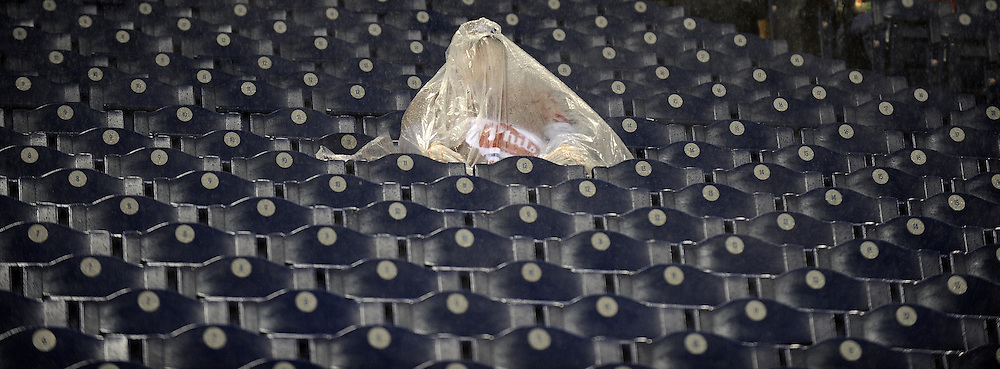 A fan sits under a poncho in the stands as heavy rain falls prior to the scheduled start of game three of the 2008 World Series between the Tampa Bay Rays and the Philadelphia Phillies at Citizens Bank Park in Philadelphia, Pennsylvania, USA 25 October 2008.  The best-of-seven series is tied 1-1.
