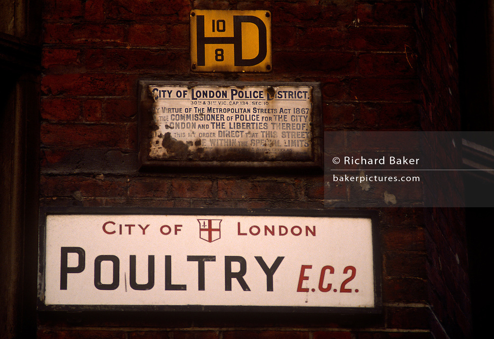 "An old City of London street sign for Poultry EC2 beneath a rusting police bylaws sign on a late 1980s brick wall. Before the older signage was replaced in the mid-1990s for more modern architecture, these signs will have disappeared or available through vintage auctions. Poultry is a short street in the City of London. It is an eastern continuation of Cheapside, between Old Jewry and Mansion House Street, near Bank junction. It takes its name, like other medieval roads nearby such as Milk Street and Bread Street, from the various produce once sold at Cheapside, meaning ""market-place"" in Old English. The street gave its name to a prison, Poultry Compter, once located there."
