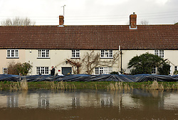 © Licensed to London News Pictures. 11/02/2014; Burrowbridge, Somerset, UK.  Burrowbridge on the Somerset levels waits for the next storm due to hit the UK in the next couple of days.  The river Parrett is high and sandbags have been put on top of the river bank.<br /> Photo credit: Simon Chapman/LNP
