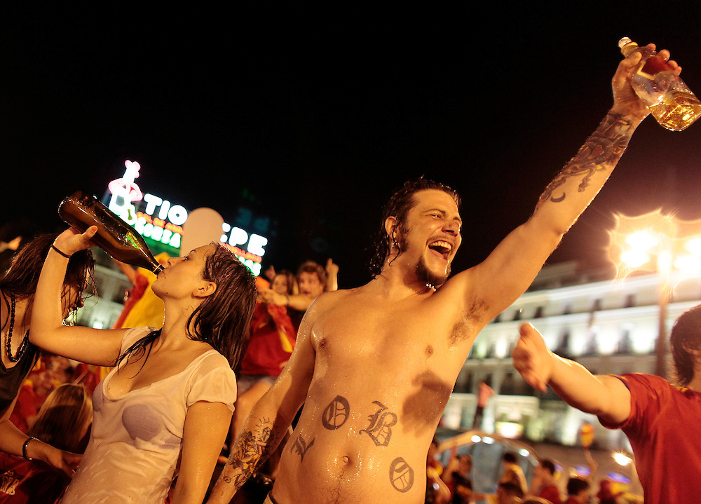 """Spanish fans celebrate in a fountain in downtown Madrid after Spain defeated the Netherlands to win the World Cup soccer final, which is being played in South Africa, on Sunday, July 11, 2010. Spain won 1-0. The man's tattoo reads """"wolf."""""""