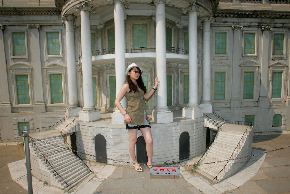 A young Chinese holiday maker poses for a snapshot at the steps of Oval office, seen here in scale model, part of a  permanent display at the World Park in Beijing, China Sunday May 6, 2007. Chinese can view scale models some of the most famous world sites without having to leave Beijing.