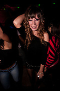 PRETTY BRUNETTE WITH CURLY HAIR FEMALE SMILING AT CAMERA IN CLUB
