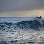 Surfer cuts back on a wave as the sun sets in Hawaii.