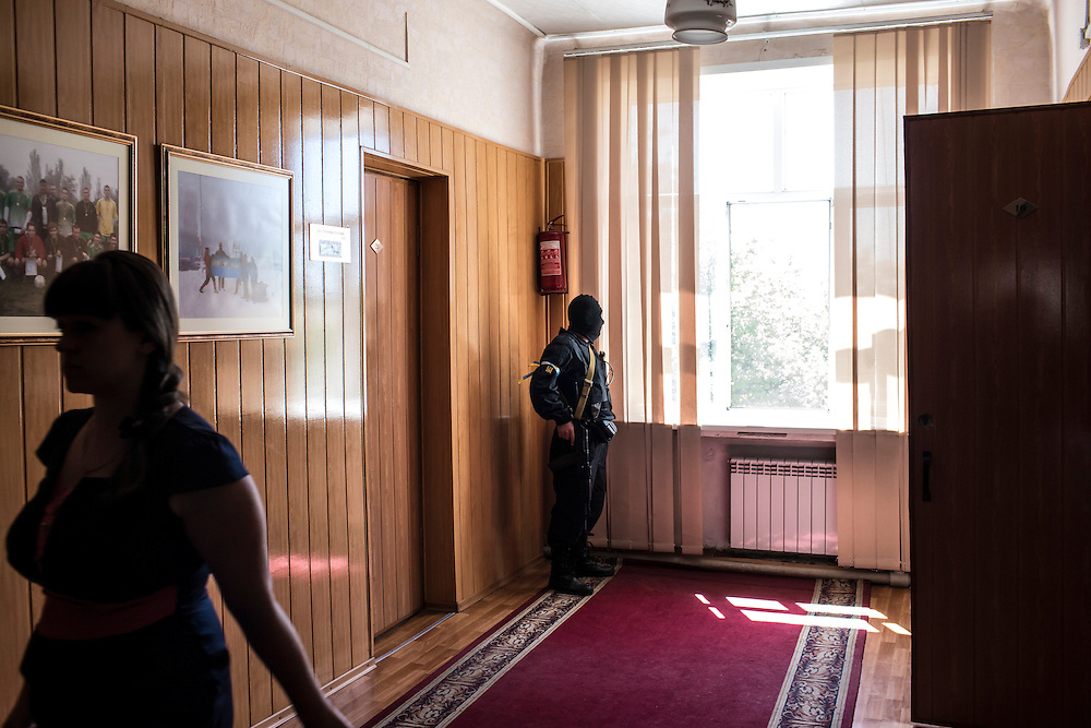DOBROPILLYA, UKRAINE - MAY 21:  A member of the Donbass Battalion, a pro-Ukraine militia, secures a hallway while others meeting with the head of the District State Administration to ensure the integrity of the upcoming presidential election on May 21, 2014 in Dobropillya, Ukraine. Days before presidential elections are scheduled, questions remain whether the eastern regions of Donetsk and Luhansk are stable enough to administer the vote. (Photo by Brendan Hoffman/Getty Images) *** Local Caption ***