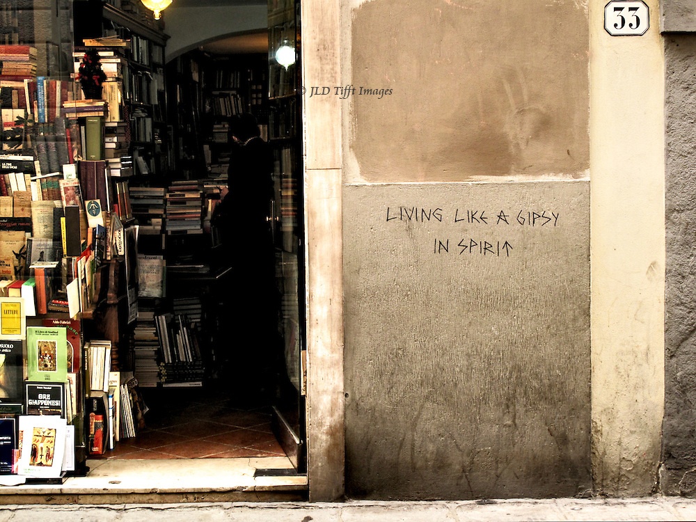 "Exterior of a bookshop with graffiti on the wall outside:  ""Living like a gypsy in spirit.""  Inside the bookshop, a customer browses in the shadows."