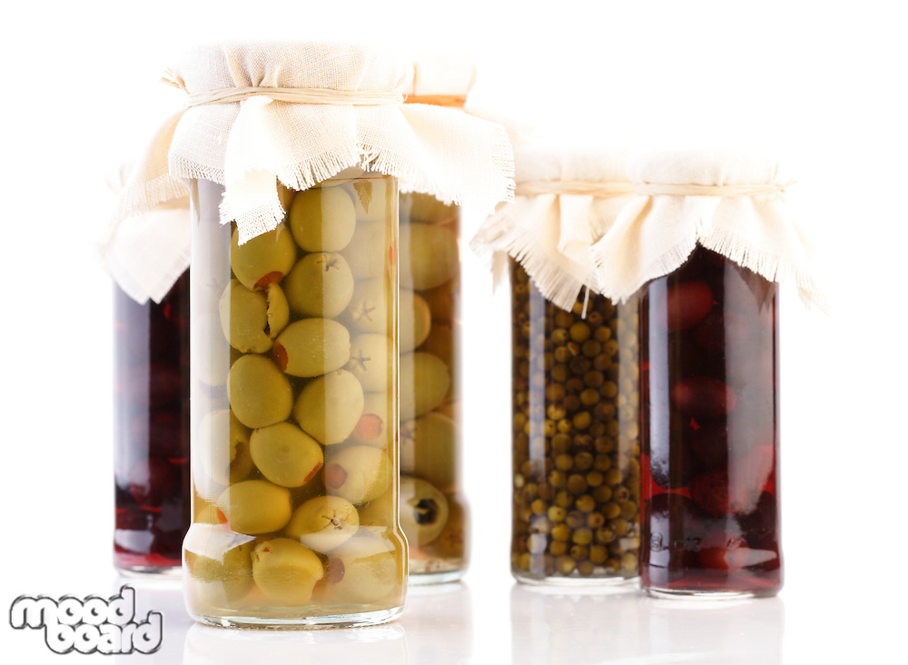 Jars with pickled olives on white background
