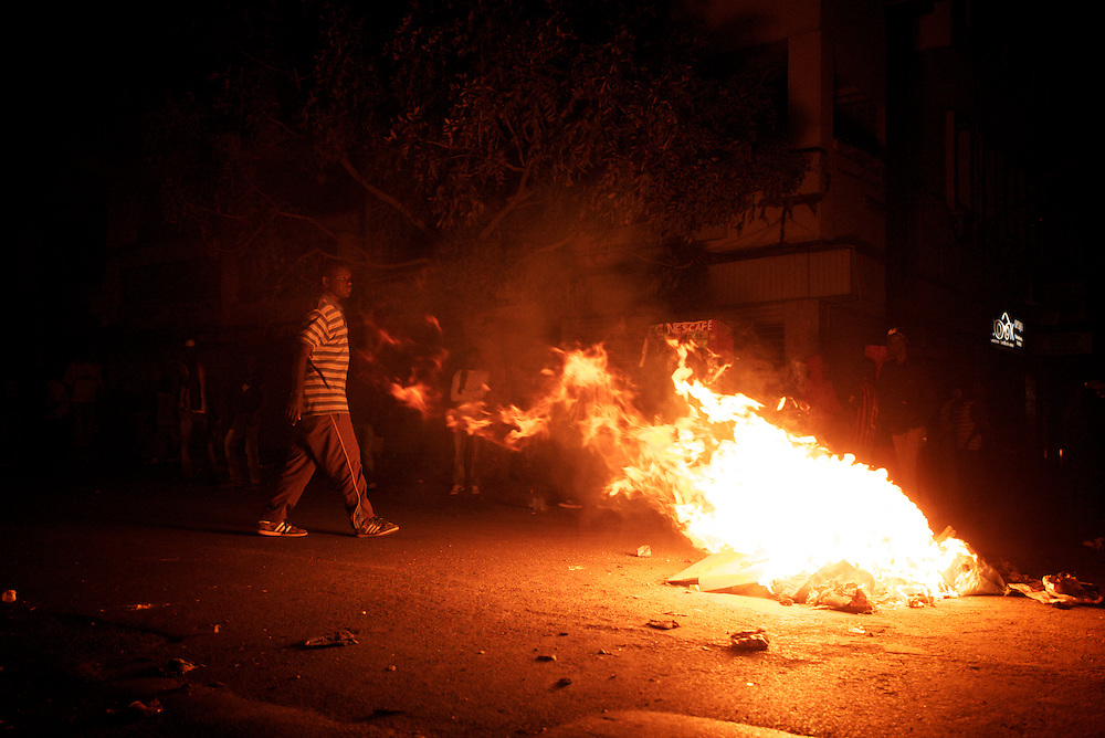 February 23, 2012 - Dakar, Senegal: A group of opposition supporters gather around a burning road block during a protest against the candidature of the current president Abdoulaye Wade for a anti-constitutional third candidature to as head of state. Tensions between police and opposition supporters have been high in the capital Dakar and other cities around the country, where some clashes have happen ahead of the presidential elections on the 26th of February. At least fourteen people have died in the past month. (Paulo Nunes dos Santos/Polaris)