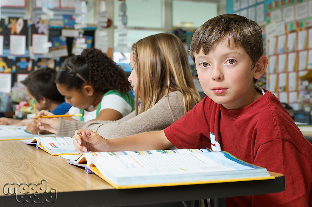 Schoolboy sitting in classroom and looking at camera