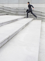 Business man running up steps outdoors side view