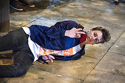 """© Licensed to London News Pictures . 16/11/2015 . Manchester , UK . A man falls in the street . Annual student pub crawl """" Carnage """" at Manchester's Deansgate Locks nightclubs venue . The event sees students visit several clubs over the course of an evening . This year's theme is """" Animal Instinct - unleash your beast """" . Photo credit : Joel Goodman/LNP"""