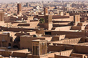 Built from mud bricks, windtowers called badgirs (Farsi), catch the wind and cool homes and other buildings. Building structures in Iran are built close together, especially in the country's hot, arid central region, and their purposefully tall earthen and brick walls create maximum shade for pedestrians in the narrow adjacent alleyways.  Yazd, Iran. Old City.
