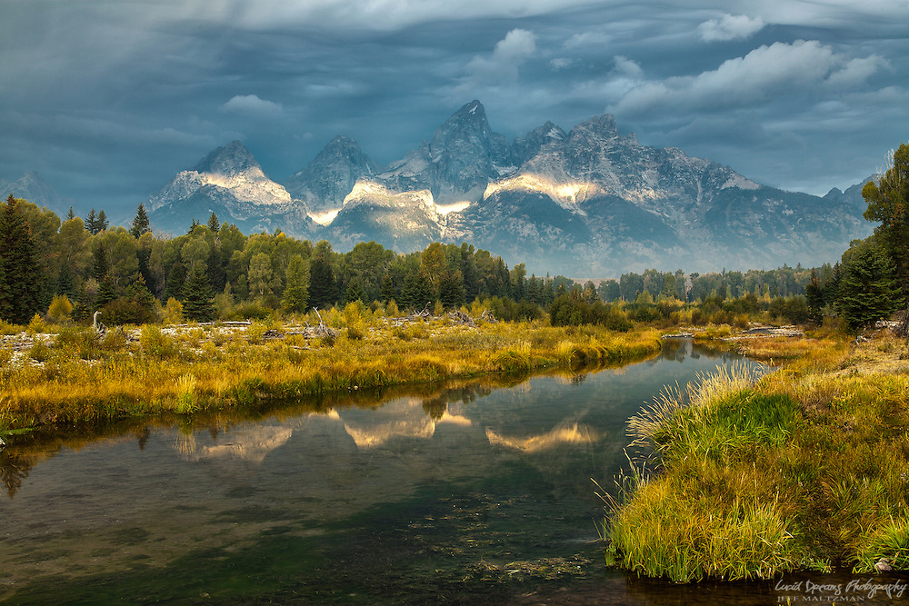 A short-lived ribbon of light breaking the storm ignites the Tetons at Schwabacher Landing.