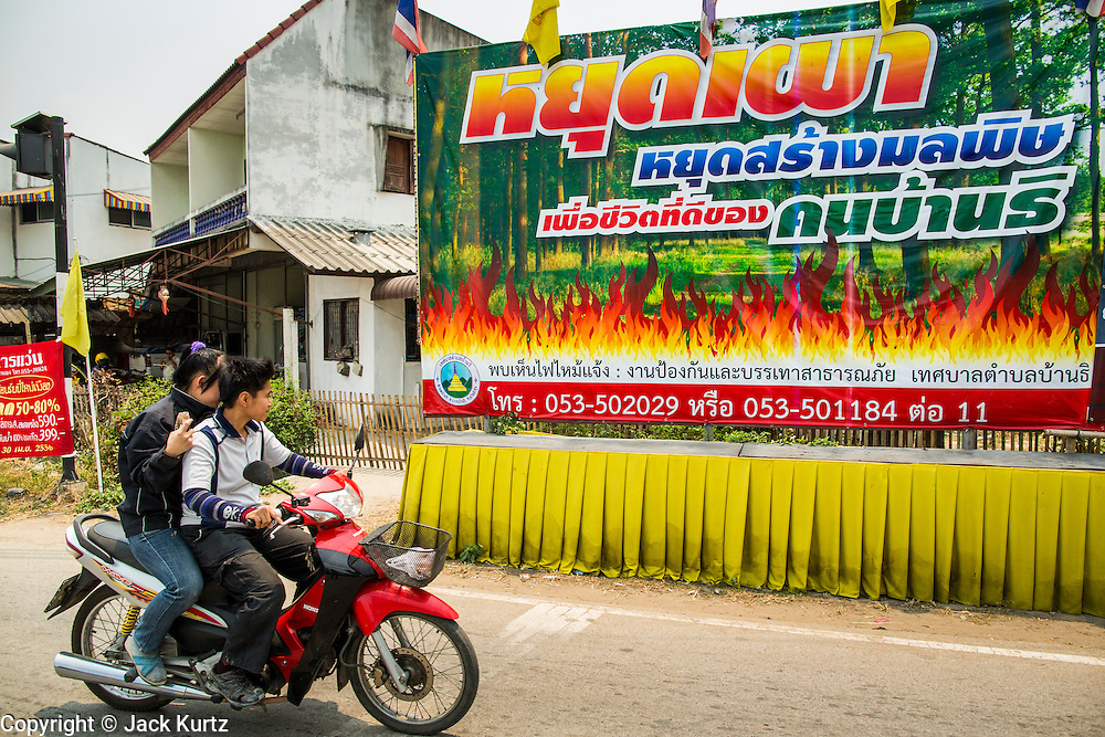 """09 APRIL 2013 - BANTHI, LAMPHUN, THAILAND:    A sign put up by the Thai government urges people not to burn the grass in their fields this year. The """"burning season,"""" which roughly goes from late February to late April, is when farmers in northern Thailand burn the dead grass and last year's stubble out of their fields. The burning creates clouds of smoke that causes breathing problems, reduces visibility and contributes to global warming. The Thai government has banned the burning and is making an effort to control it, but the farmers think it replenishes their soil (they use the ash as fertilizer) and it's cheaper than ploughing the weeds under.    PHOTO BY JACK KURTZ"""
