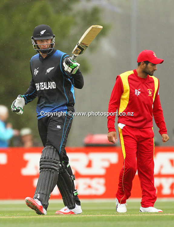 Martin Guptill of the Black Caps raises his bat after reaching a century during the ICC Cricket World Cup warm up game between the Black Caps v Zimbabwe at Bert Sutcjliffe Oval, Lincoln, Christchurch. 9 February 2015 Photo: Joseph Johnson / www.photosport.co.nz