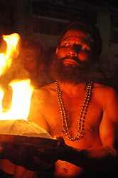 India, Gokarna, 2006. A Keralan Hindu priest carries the symbolic birth fire backwards for over five miles to initiate the evening?s prayers.