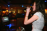 A young woman singing Karaoke at Varsity, Cardiff, Wales, UK 2006