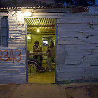 A family shelter inside their wood shack as night falls on Imizamo Yethu shanty town, Hout Bay, Cape Town, South Africa. The work of the CPF and neighbourhood watch have seen the crime rate in Hout Bay drop 63%, but relations between the shanty town of Imizamo Yethu and Hout Bay are tense.  photo  Leonie Marinovich