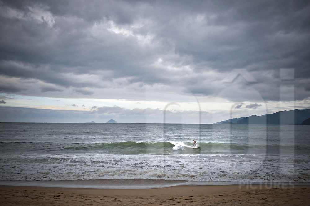 Lone surfer catches a wave on Nha Trang beach in winter, Khanh Hoa Province, Vietnam, Southeast Asia