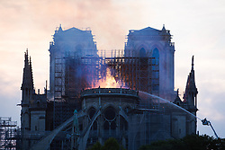 Bystanders look on as flames and smoke are seen billowing from the roof at Notre-Dame Cathedral with river in Paris on April 15, 2019. A fire broke out at the landmark Notre-Dame Cathedral in central Paris, potentially involving renovation works being carried out at the site, the fire service said.Images posted on social media showed flames and huge clouds of smoke billowing above the roof of the gothic cathedral, the most visited historic monument in Europe. Photo by Raphael Lafargue/ABACAPRESS.COM