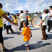 As a band of school students marches by, a young boy enjoys the parade. The procession, on 15 September 2011, was part of the celebrations for Guatemalan Independence Day. Groups of school students parade in a procession through the streets of Flores, starting in the Parque Central, walking through the town, and crossing the causeway into Santa Elena.