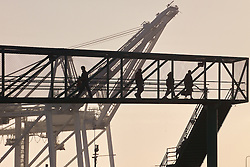 Shift Change at the Port of Long Beach at Sunset. Cranes and Crews. Workers Silhouettes crossing Pedestrian Bridge.