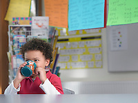 Boy drinking from cup in classroom