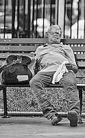 A man takes a nap on a park bench during