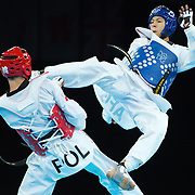 Rohullah Nikpah of Afghanistan, right, delivered a kick to Michal Loniewski of Poland, left, in men's 68kg taekwondo action at the ExCeL centre during the 2012 Summer Olympic Games in London, England, Thursday, August 9, 2012. Nikpah won the bout 12-5. (David Eulitt/Kansas City Star/MCT)