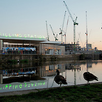 London construction site at King's Cross station with high cranes against night sky with restaurant on canal and Canadian geese