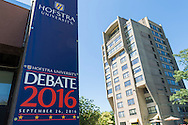 Hempstead, New York, USA. September 13, 2016. Hofstra University Debate 2016 banner - tall vertical in patriotic red white and blue - is one of many displayed on the campus of Hofstra University, which will host the first Presidential Debate, between H.R. Clinton and D. J. Trump, scheduled for later that month on September 26. A high-rise residence hall is at right, also in North Campus. Hofstra is first university ever selected for 3 consecutive U.S. presidential debates.