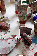 close up of the table with paint and tools in an artist studio