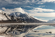Icebergs break up the reflection of the Chugach Mountains in Turnagain Arm at high tide in Southcentral Alaska. Winter. Afternoon.