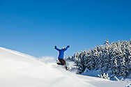 A hiker on snowshoes jumps down a hill of powdery snow on a sunny blue-sky day at Turnagain Pass in the Chugach National Forest of Southcentral Alaska. Winter. Afternoon. MR.