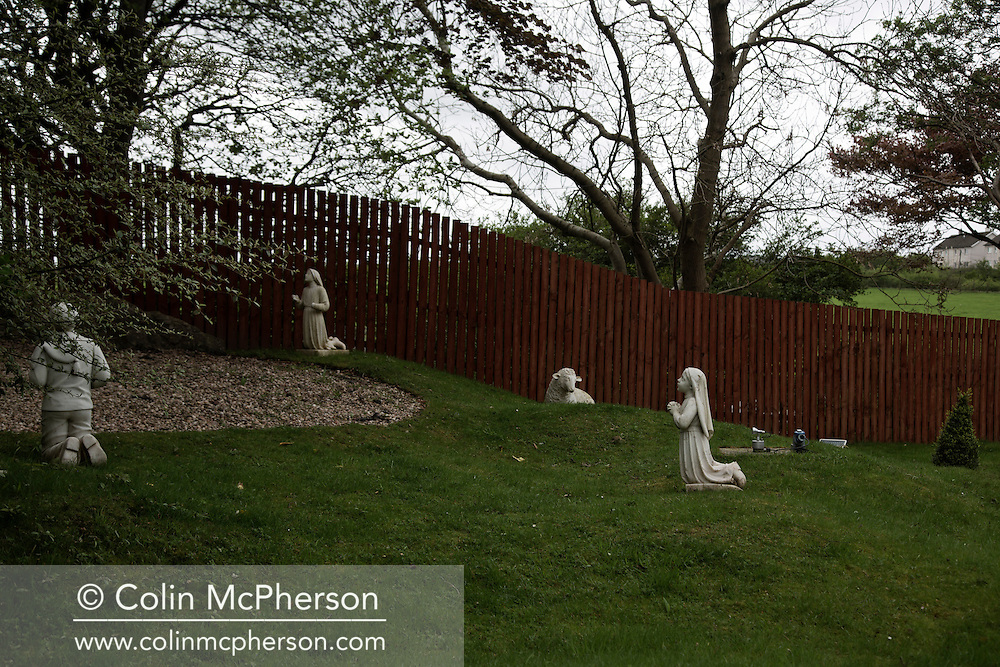 'Untitled, 2014' from the project 'The Fall and Rise of Ravenscraig' by photographer Colin McPherson.<br /> <br /> The photograph shows devotional statues at the Carfin Grotto after a service in one of the site's chapels. The Grotto is located at the northern end of the former steelworks at Ravenscraig.<br /> <br /> This project, photographed in 2014, looks at the topography of the post-industrial landscape at Ravenscraig, the site until its closure in 1992 of the largest hot strip steel mill in western Europe. In its current state, Ravenscraig is one of the largest derelict sites in Europe measuring over 1,125 acres (4.55 km2) in size, an area equivalent to 700 football pitches or twice the size of Monaco. It is currently being developed with a mix of housing, retail and the home of South Lanarkshire College and the Ravenscraig Regional Sports Facility.