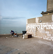 With a calm sea behind, a father cares to his child at the end of the harbour at Margate, the hometown of Britpop artist Tracy Emin, whose name appears in paint on the wall.