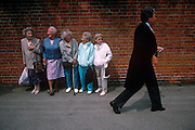 Five elderly women on-lookers are lined against a wall outside the famous Ascot race course on Ladies' Day, the annual event on the English sporting and social calendar in June. Each are standing in order of size, from tallest (who holds a Tesco supermarket bag) to smallest and watch as a man dressed in formal tails walks towards an entrance gate for the private members' enclosure. We see the two sides of the class system but it is a humerous scene. There is good nature between the two groups with smiles exchanged with one couple but discomfort from those behind.