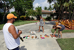 31 July 2015. Marco Island, Florida.<br /> L/R;  Protesters Edmar Amaya (an animal rights attorney), Gianna Solarte (a dentist) and Daniella Melo (a vet) put down stuffed animals spelling out the word 'KILLER' outside the deserted Florida home of Dr Walter Palmer. Palmer is the Minnesota dentist who allegedly killed Cecil the lion in Zimbabwe. Dr Palmer has gone to ground since the story broke, taking him from hunter to hunted.<br /> Photo; Charlie Varley/varleypix.com