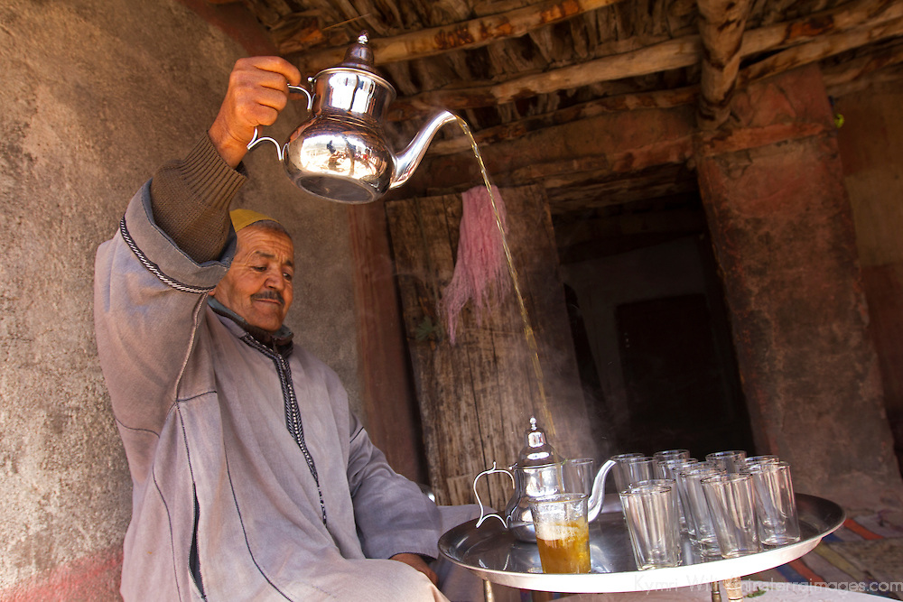 Africa, Morocco, Imlil. Berber man pouring tea at home in the village of Asni in the Atlas Mountains.